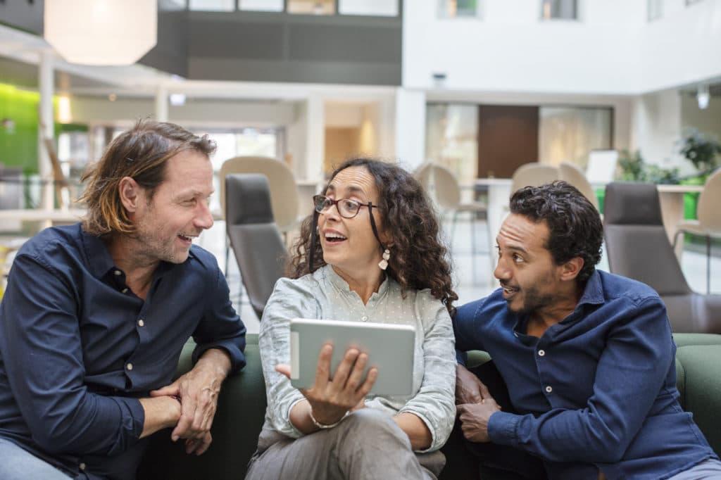Tre mennesker som snakkersammen  foran en skjerm