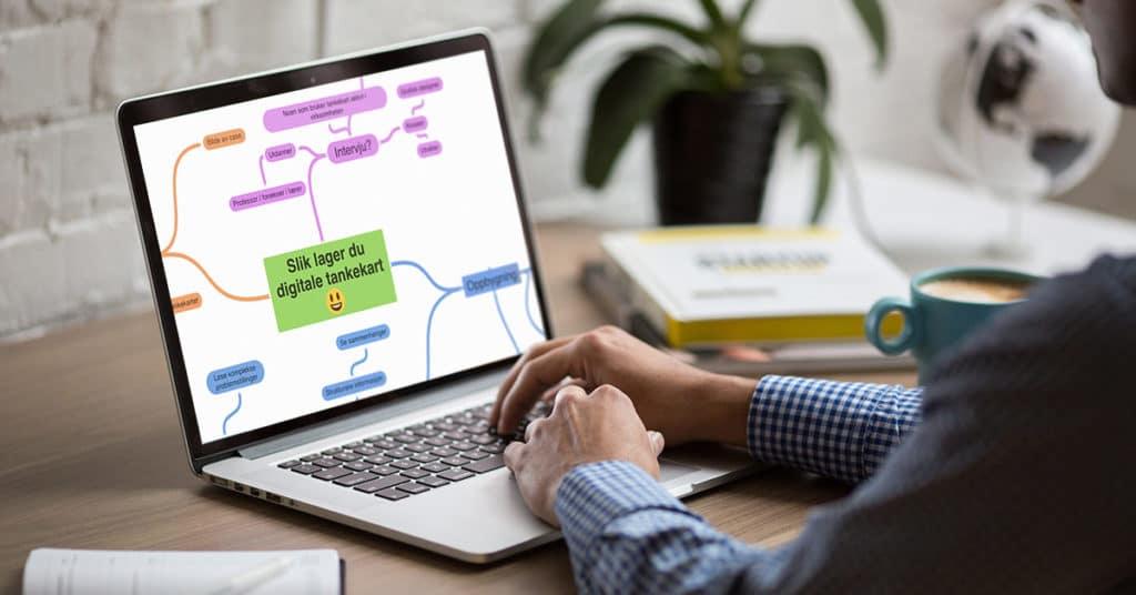 En person lager et digitalt tankekart på en laptop som står på en pult.